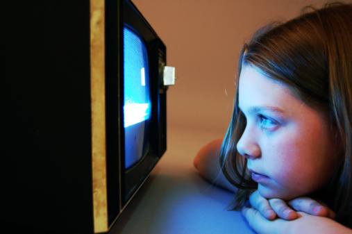 Child laying on stomach watching a blank tv screen